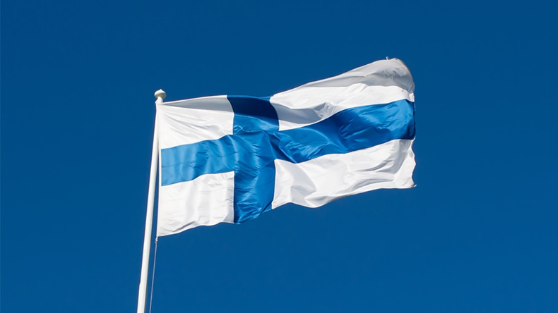 Flag of Finland flies against a blue sky