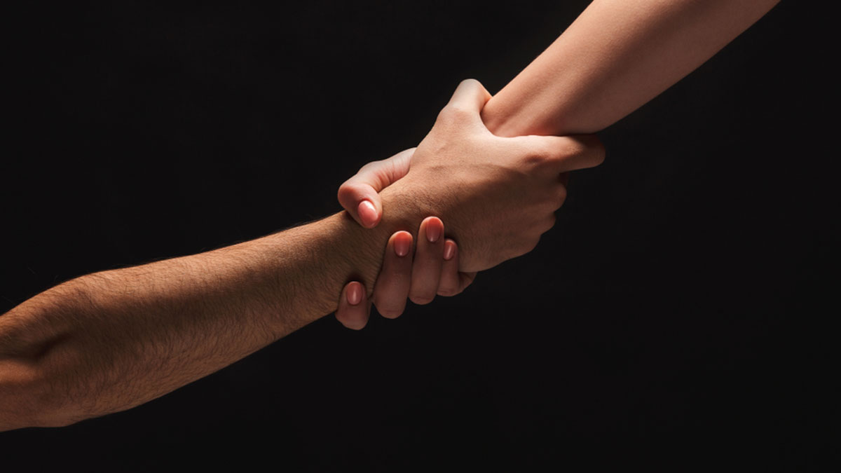 Male and female hands holding tight together on black isolated background. Love, relations, support, together forever concept. Copy space, cutout, low key