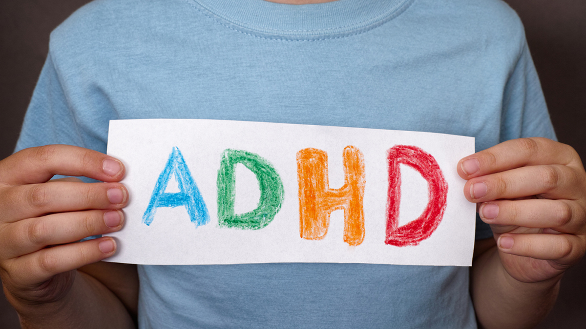 Young boy holds ADHD text written on sheet of paper. ADHD is Attention deficit hyperactivity disorder. Close up. - Image
