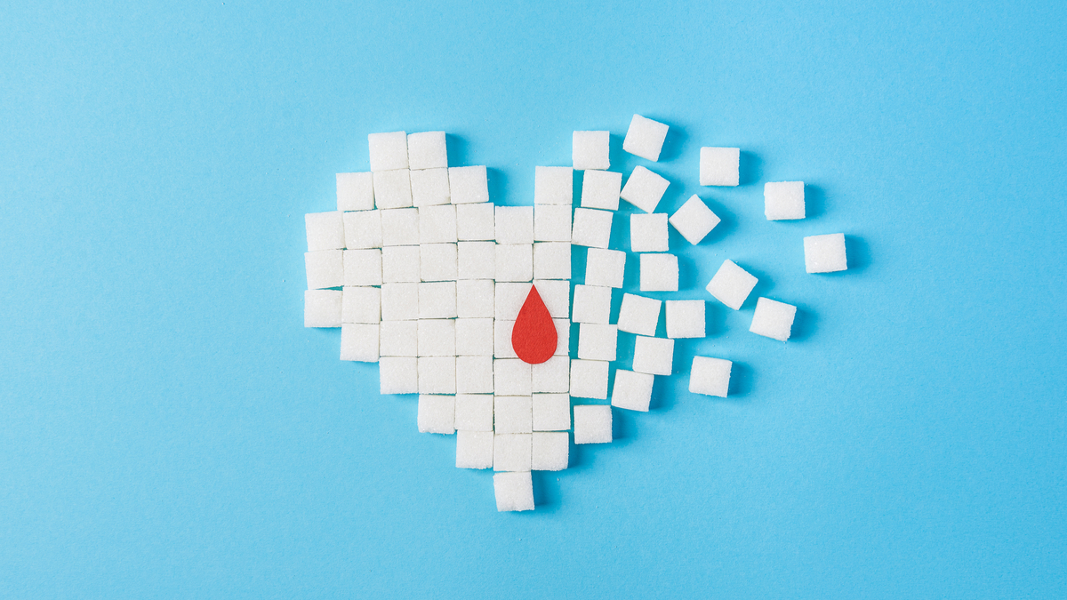 the drop of blood on broken heart made of pure white cubes of sugar isolated on blue background, World diabetes day, November 14 - Image