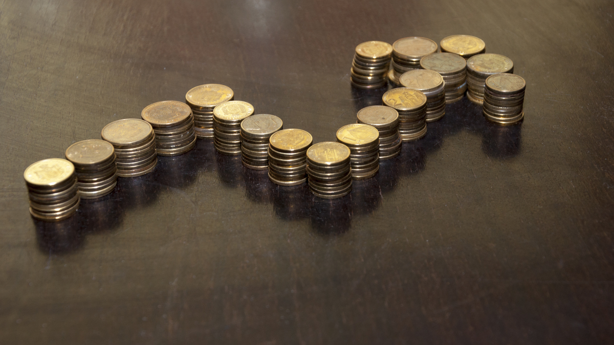 Coins stacked on each other in shape of arrow. Concept of success. - Image