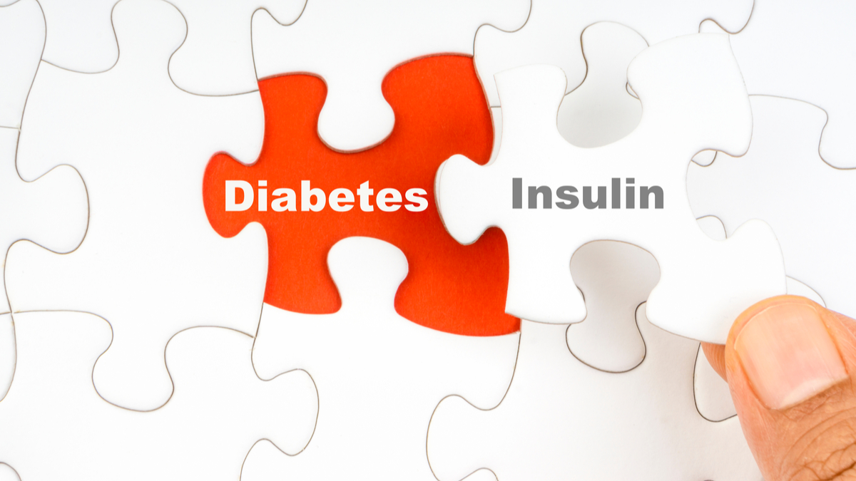 Hand holding piece of jigsaw puzzle with word DIABETES INSULIN. Selective focus - Image