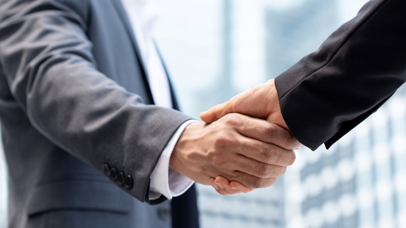 Businessmen making handshake outdoors in city office building background for merger and acquisition concept - Image
