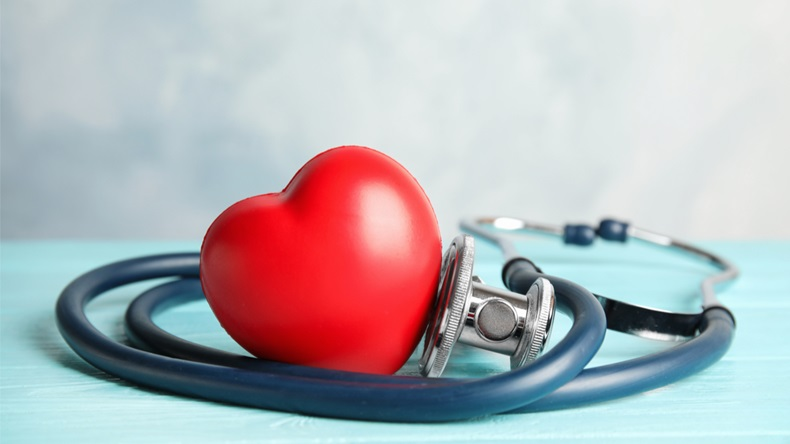 Stethoscope and red heart on wooden table. Cardiology concept - Image