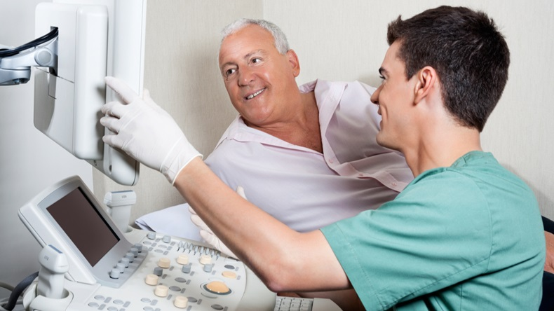 Male technician showing ultrasound machine's monitor to senior patient - Image