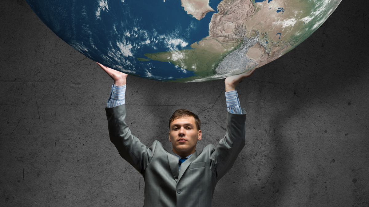 Young businessman holding Earth planet high above head. Elements of this image are furnished by NASA - Image
