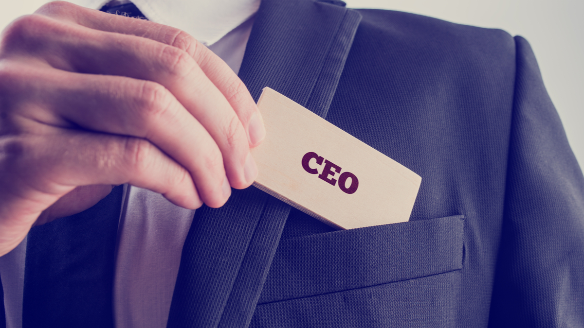 Retro style image of a businessman showing a wooden card reading - CEO - as he withdraws it from the pocket of his suit jacket. - Image