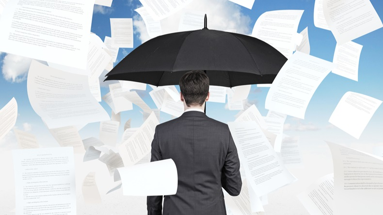 businessman is standing under the papers rain.
