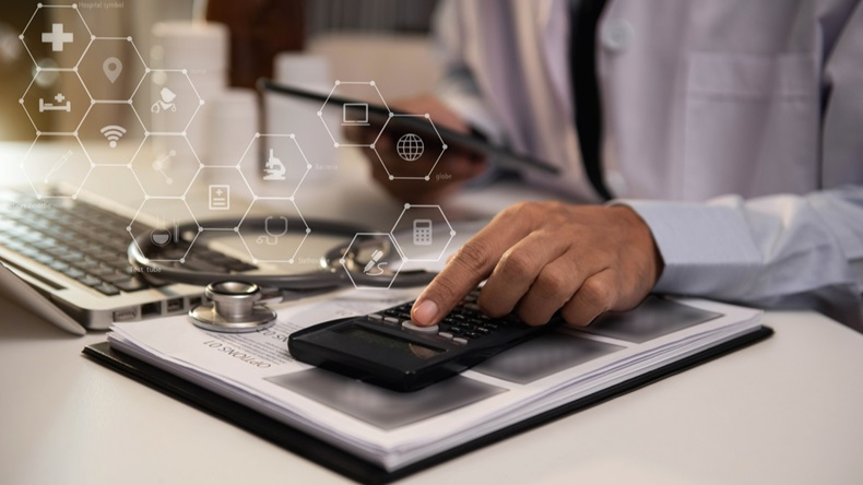 Doctor or accounting department writes a note and uses a calculator to calculate expenses - income.