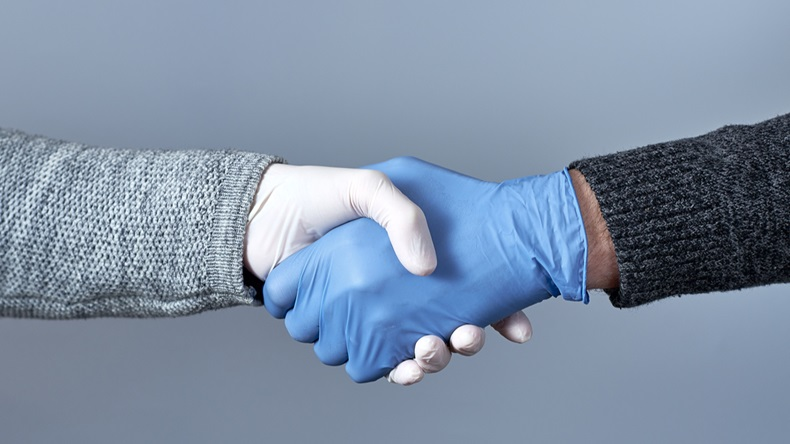 The concept of a safe handshake. Shaking hands in medical gloves on gray background