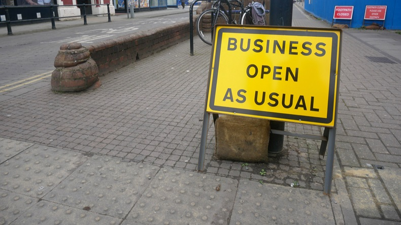 'Business open as usual' sign on British street showing concept of economic recovery