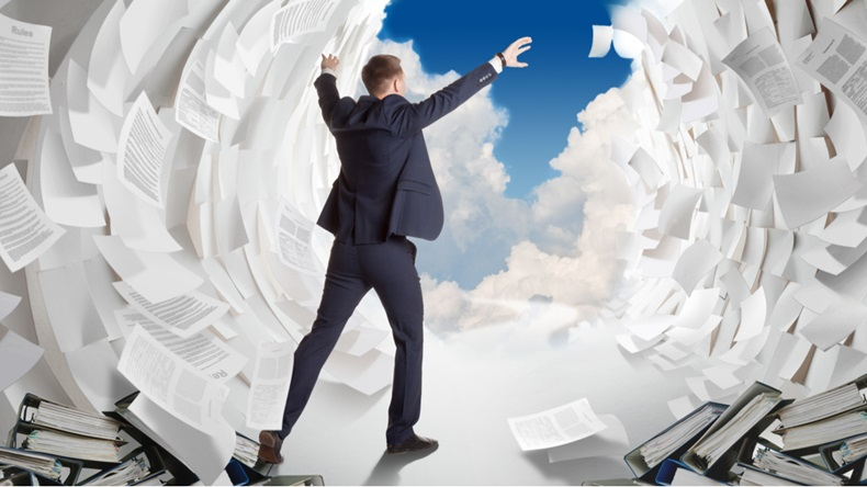 Man in suit parts waves of paperwork to see clear sky beyond.