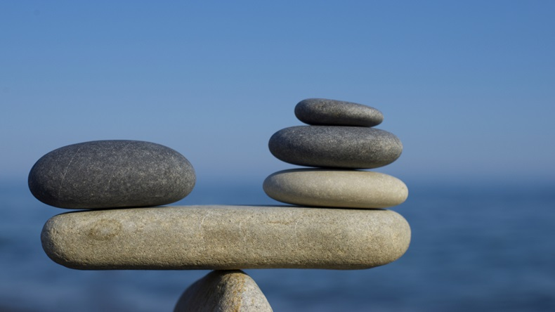 Balancing stones on a blue sky and sea background.