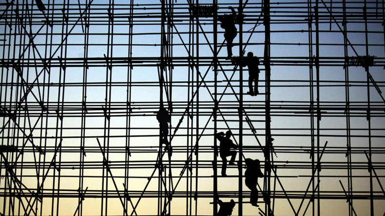 Construction workers climb scaffolding against an evening silhouette.