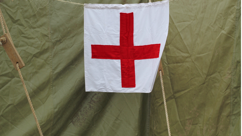 The sign of the red cross on a canvas army tent. Mobile military hospital.
