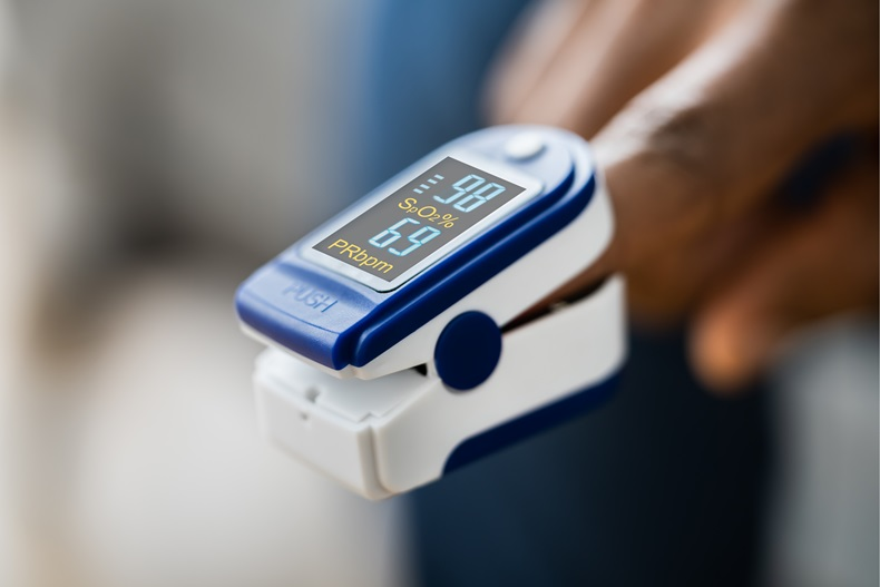 A pulse oximeter clipped onto the finger of an African-American person.