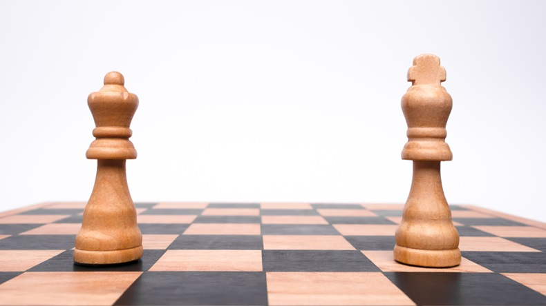 A king and a queen stand in isolation at different ends of a chessboard.