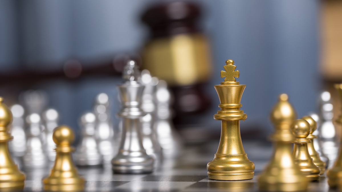 Close up golden chess pieces with blurry judge gravel and law book background.