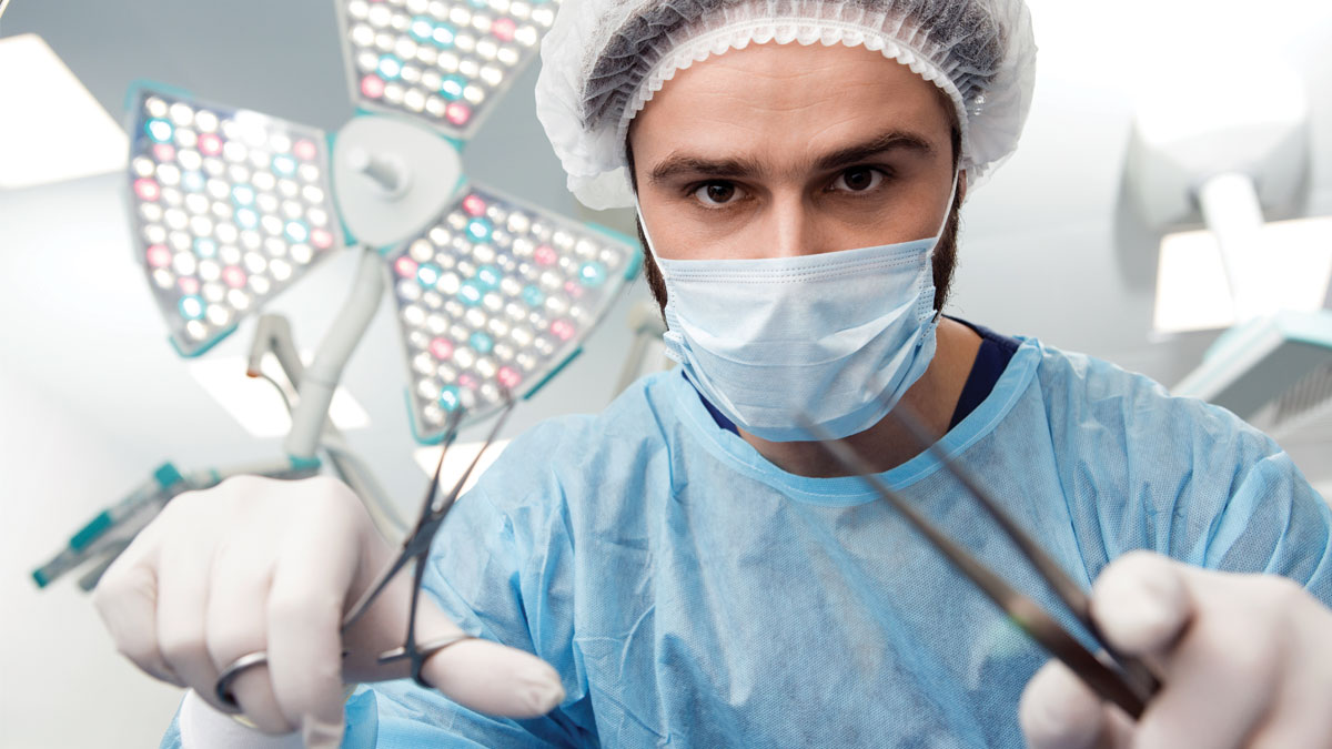Nothing to be scared of! Professional male surgeon wearing protective uniform looking at the camera with surgical instruments in his hands surgical lamp on the background copyspace doctor medical job