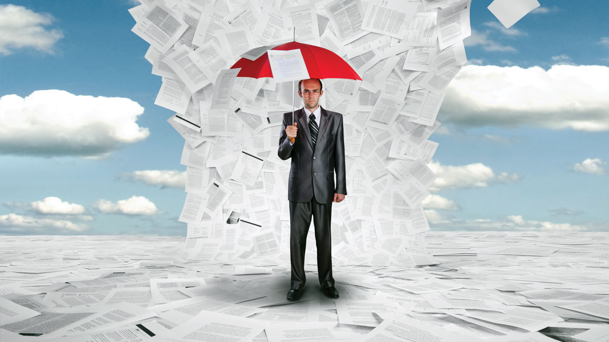 Serious businessman with red umbrella under huge wave of documents