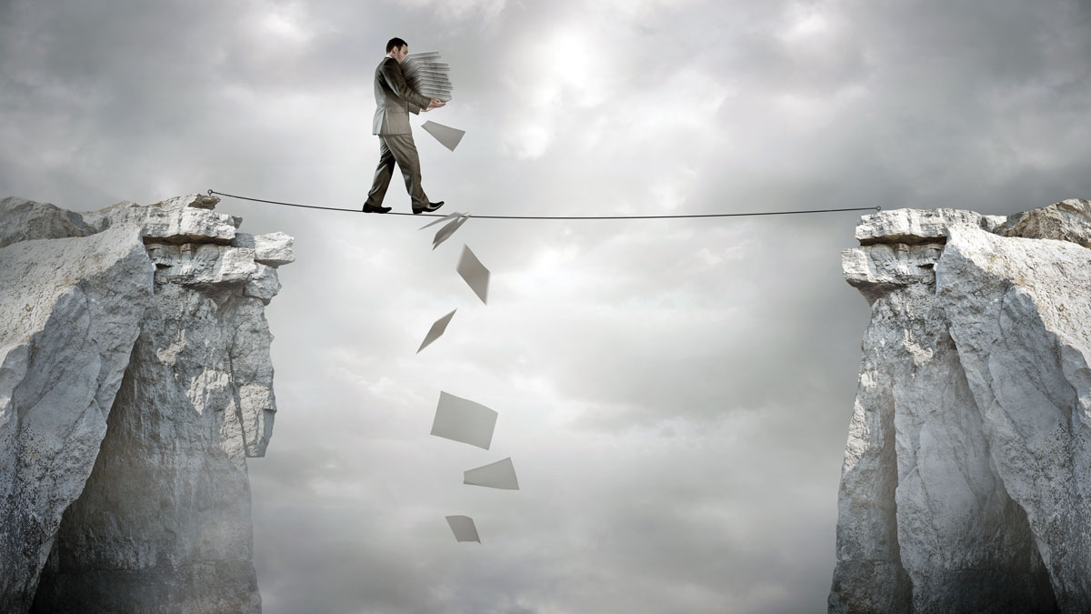 Business Balance - A businessman carrying paperwork walking over a tight rope.
